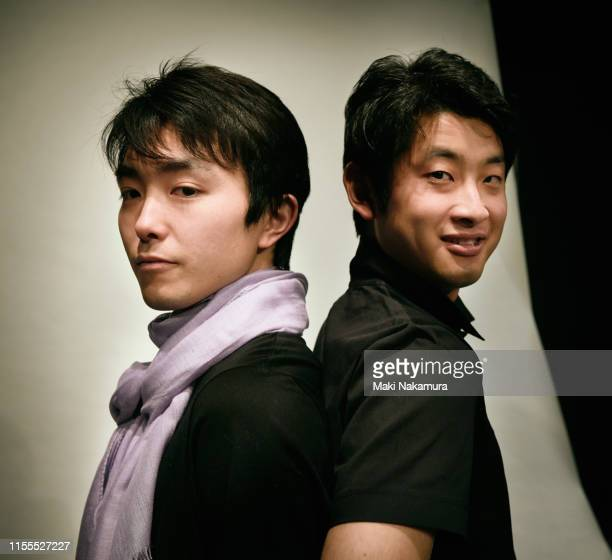 two millennial generation men are smiling back to back - 背中合わせ ストックフォトと画像