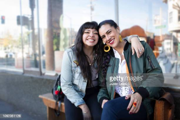 two millennial latina women lean into each other, smiling, while sitting on a bench - zus stockfoto's en -beelden