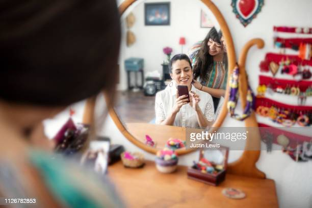 two millennial latinas prepare for event, one uses smartphone while her partner braids her hair, portrait reflected in dressing table mirror - social media marketing stock pictures, royalty-free photos & images
