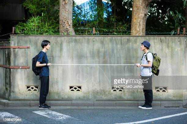 two millennial men keeps social distancing of 2 meters - covid-19 ストックフォトと画像