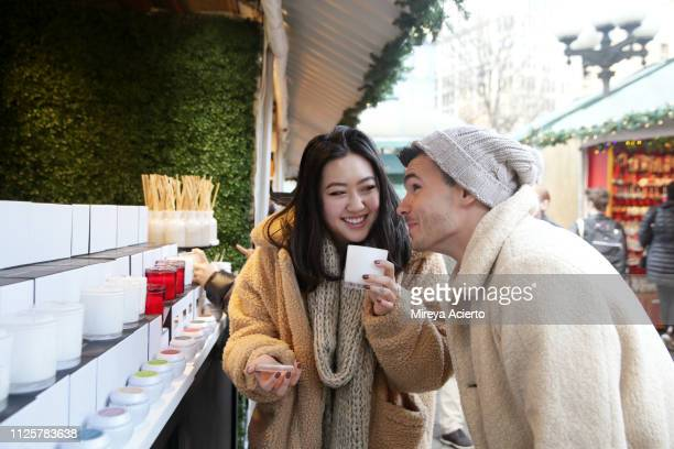 two millennials, one caucasian male and one asian female, shop for candles at outdoor holiday market in the city. - cream colored coat stock pictures, royalty-free photos & images