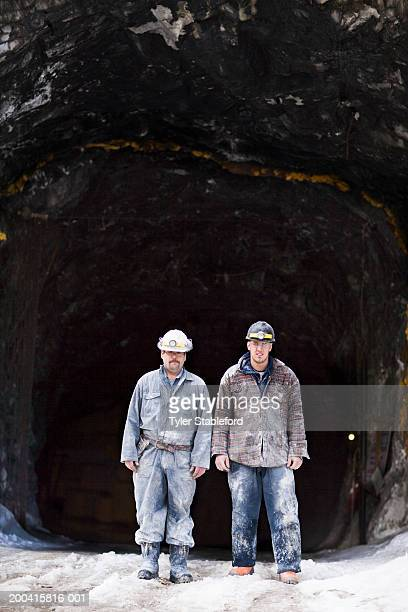 Two miners in hardhats at entrance to mine