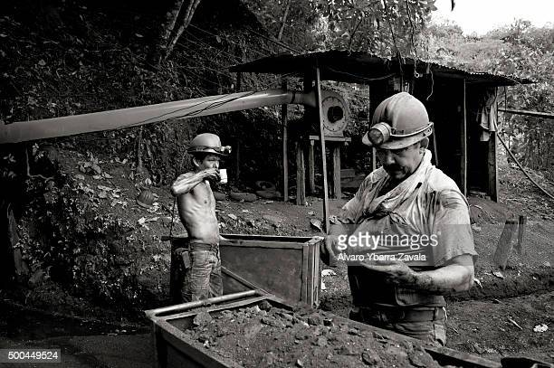 Two miners search through mined rubble in search of emeralds at the entrance to the Millionaire mine The miners work simply for food spending 12...