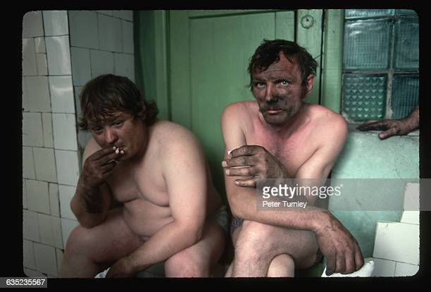 Two miners sit in a shower room after their shift They live in a poor coalmining and steelmanufacturing town enduring widespread economic hardships