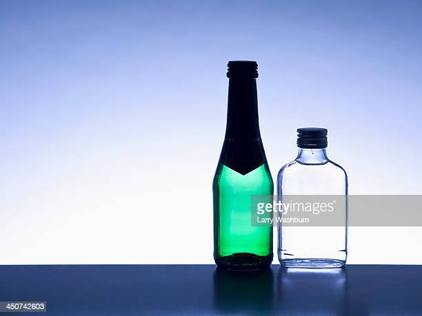 Two miniature bottles of alcohol side by side without labels, back lit