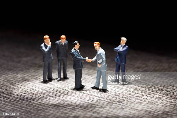 Two miniature businessmen figurines shaking hands amongst other businessmen figurines