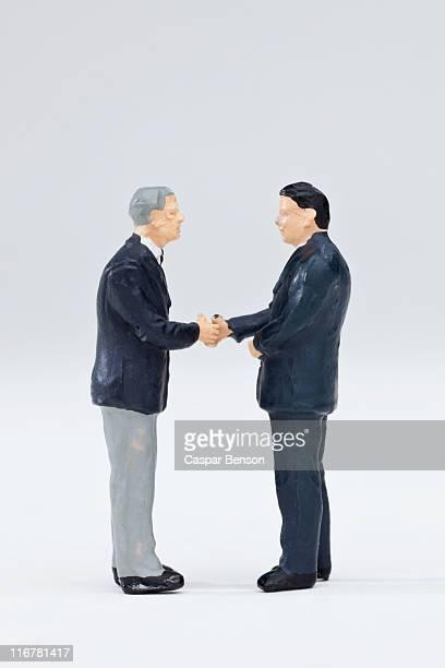 Two miniature businessmen figurines shaking hands