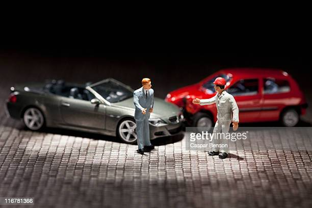 Two miniature figurine men arguing over their miniature crashed cars