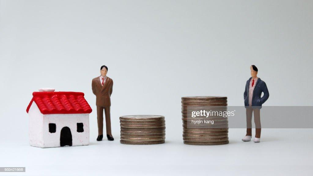 Twee mannen in miniatuur permanent naast een stapel van munten en miniatuur huis. : Stockfoto