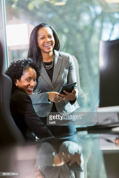 two minority businesswomen meeting in board room - minority groups stock pictures, royalty-free photos & images