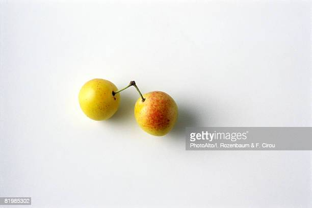 Two mirabelle plums, white background