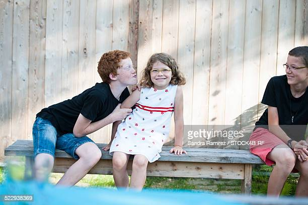 two mischievous boys and girl on a bench - 10 11 ans photos et images de collection