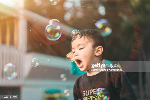 Two mixed race kids blowing bubbles in backyard.