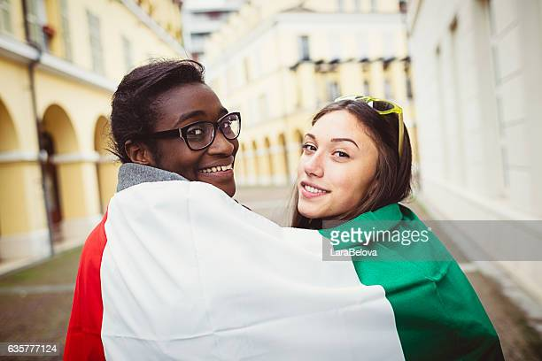 Two mixed race young women covered by Italian flag