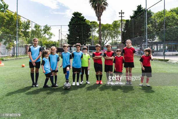 two mixed soccer teams in a row together - football team stock pictures, royalty-free photos & images