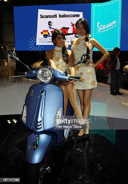 Two model poses on a Vespa Piaggio motorbike during the EICMA 2013 71st International Motorcycle Exhibition on November 6 2013 in Milan Italy