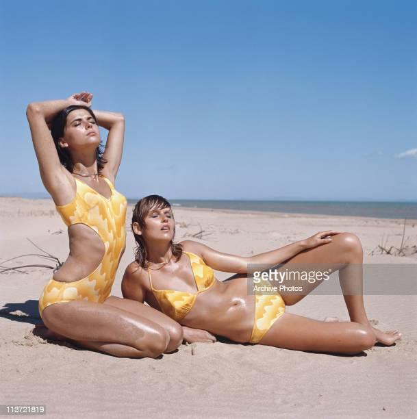 Two model wearing matching yellow swimwear on the beach 1970