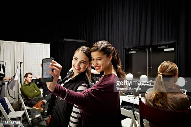 Two models backstage at fashion show taking photo