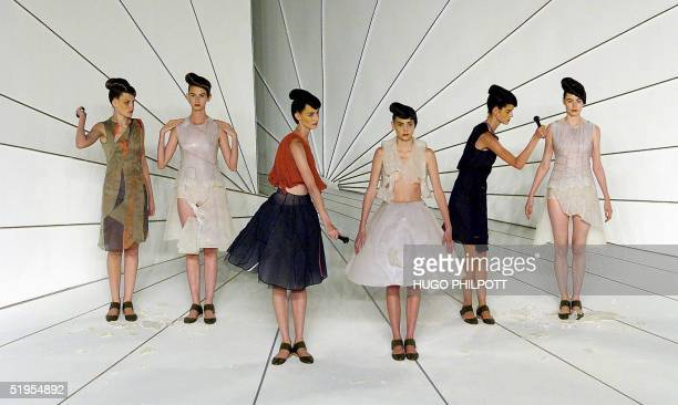 Two models chip away at two models presenting creations by designer Hussein Chalayan for the Spring/Summer 2001 collection at London Fashion Week 27...
