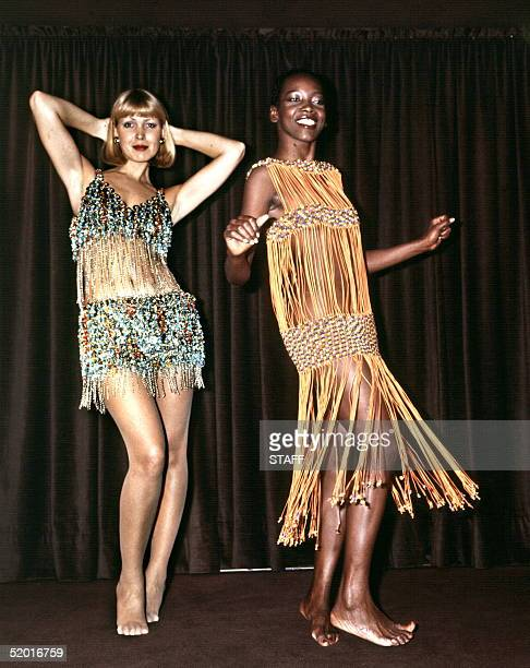 Two models display 24 January 1976 in Paris at right a long African dancing dress made of orange cotton strips glass beaded bra and waist bands at...