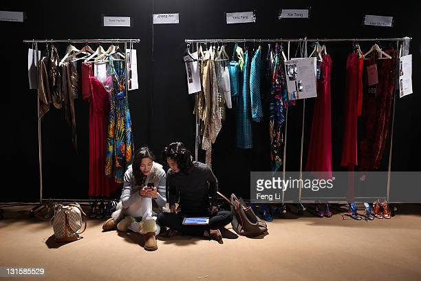 Two models have a rest before the Salvatore Ferragamo Spring Summer show at the Ullens Centre for Contemporary Art on November 5 2011 in Beijing China