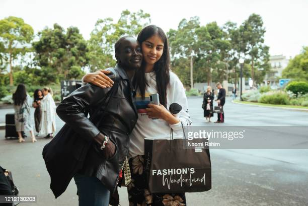 Two models hug outside the Royal Exhibition Building after the announcement of the cancelled fashion show on March 13 2020 in Melbourne Australia...