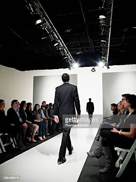 two models in business suits walking on catwalk - catwalk stock pictures, royalty-free photos & images