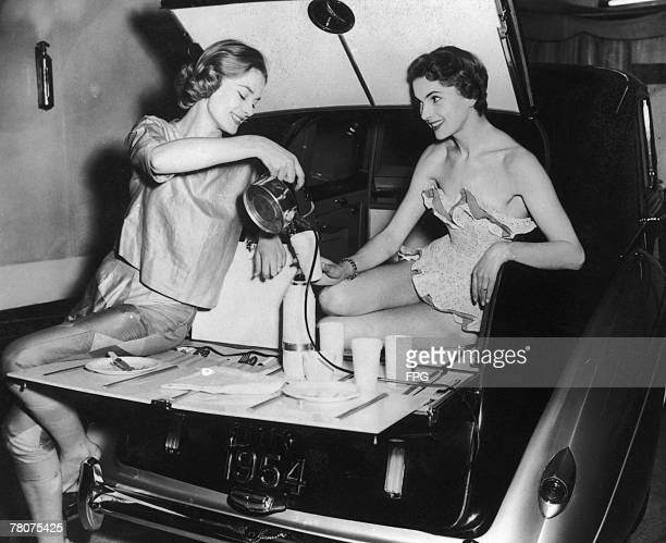 Two models making tea on an extendable picnic table in the boot of a Bentley saloon 1954