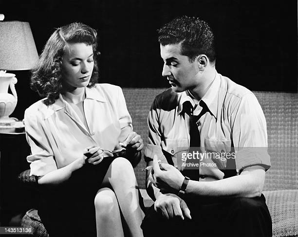 Two models pose as drug users preparing a shot of heroin circa 1952