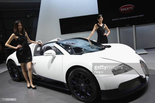 Two models pose beside the Bugatti 16.4 Super Sport during the media day of the Shanghai International Automobile Industry Exhibition at Shanghai New...