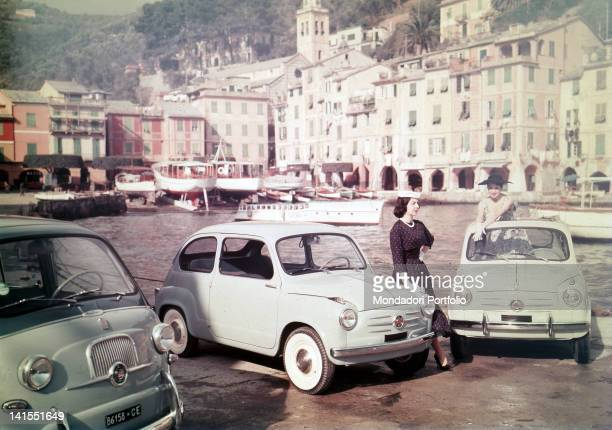 Two models posing in the port among three new Fiat 600 cars Portofino 1955