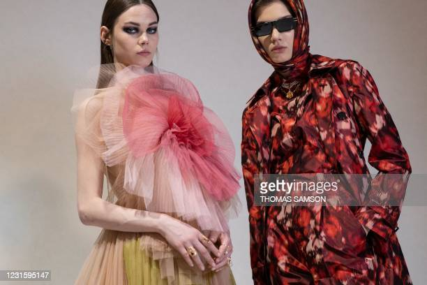 Two models present creations for Christian Dior during the presentation of the Fall/Winter 2021 ready-to-wear fashion collection, on March 6 in...