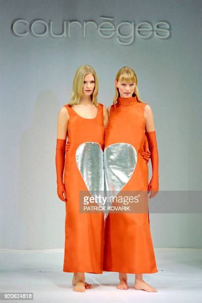 Two models present French fashion designer Courreges' twin look anklelength orange gazar dresses in a 'heart' motif with a tank top or turtleneck...