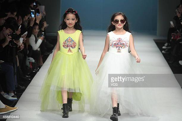 Two models showcase designs on the runway at Showkids 'Liu Jia Children' Collection show during the MercedesBenz China Fashion Week Spring/Summer...