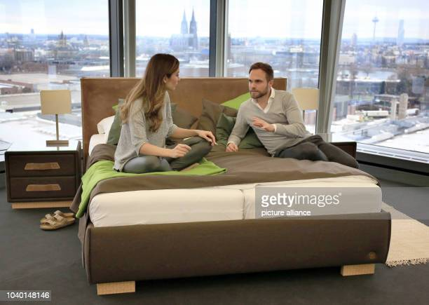 Two models sitting on an 'Canberra' bed manufactured by Birkenstock in Cologne Germany 11 Janaury 2017 The International Interiors Show  is being...