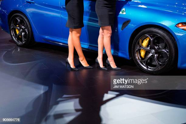 Two models stand near the Alfa Romeo Giulia during the 2018 North American International Auto Show in Detroit Michigan on January 15 2018 / AFP PHOTO...