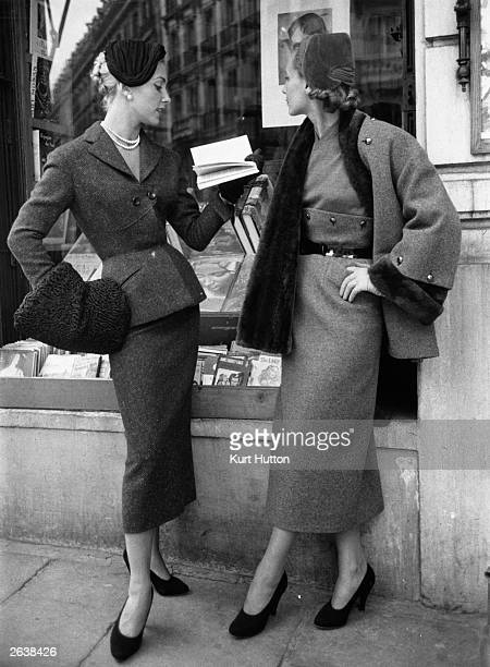 Two models standing outside a bookshop wearing tweed suits from French designer Pierre Balmain's autumn/winter collection a red suit with black...