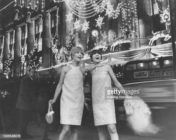 Two models standing outside the Selfridges department store, wearing dresses by French designer Piere Cardin and admiring the Christmas lights on...
