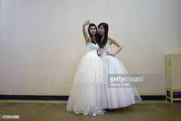 Two models take a photo backstage during a wedding expo in Beijing on February 28 2014 Unlike in the west Chinese wedding photos are normally taken...