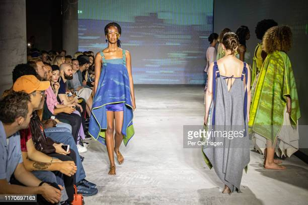 Two models walk the runway at the viewing of Norwegian designer Tonje Plur's designs at the Fushion Fashion Art Festival on August 28 2019 in Oslo...