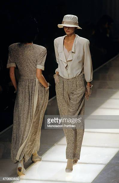 Two models walking down the catwalk with refined beige dresses by Armani Milan 1986
