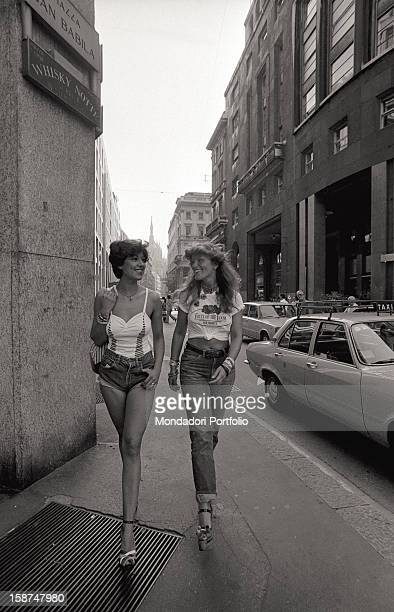 Two models walking in Corso Vittorio Emanuele and wearing clothes designed by Italian fashion designer and entrepreneur Elio Fiorucci. Milan, 1974