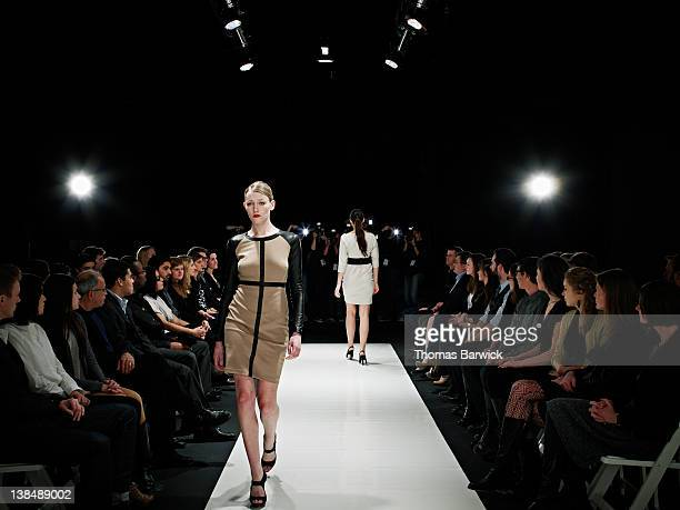 Two models walking on catwalk during fashion show