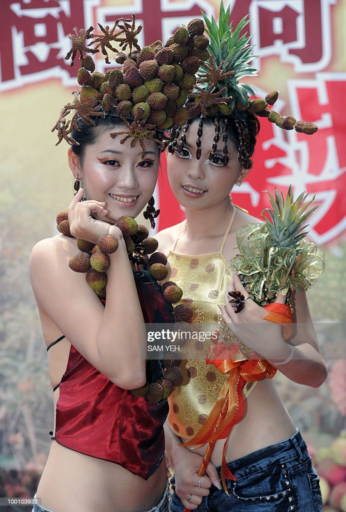 Two models wear lychee hats during a press conference in Taipei on May 21, 2010. The event is organized by Ksohisung county, southern Taiwan, government to promote the lychee festival which will fall on May 29 - 30. AFP PHOTO/Sam YEH