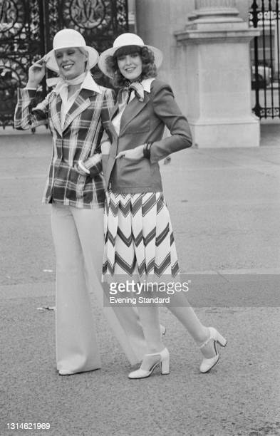 Two models wearing a checked jacket and white flares, and a blazer with a pleated skirt, UK, 29th March 1974.