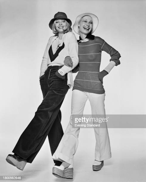 Two models wearing wide-legged trousers, sweaters and hats, UK, 14th January 1973.