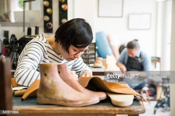 Two modern cobblers working in their small shoe shop