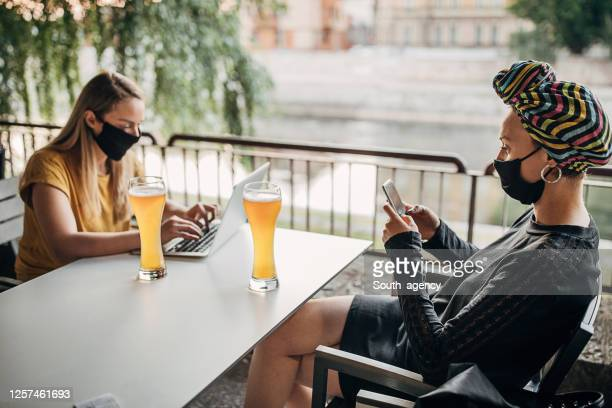 two modern women with black face masks sitting in cafe outdoors - south_agency stock pictures, royalty-free photos & images