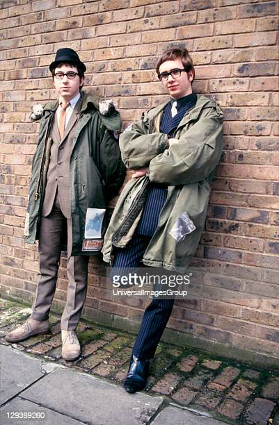 Two Mods in suits and parkas, leaning against a wall, London, UK, 2000's