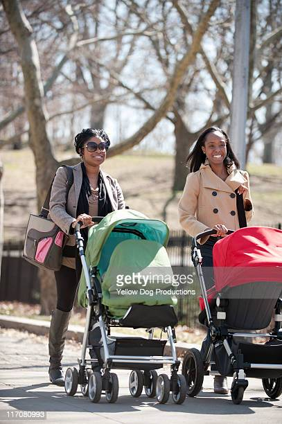 Two moms pushing babies in strollers in the park